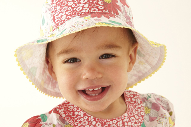 toddler in hat smiling